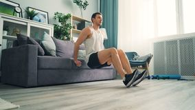 Studente maschio che fa le immersioni di flessione con il sofà a casa facendo uso dello strato per culturismo video d archivio