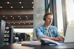 Studente maschio che lavora al computer portatile alla biblioteca pubblica Immagine Stock
