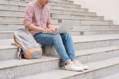 Studente maschio che lavora al computer portatile in università Fotografia Stock