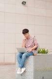 Studente maschio che lavora al computer portatile in università Immagine Stock