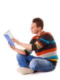 Studente maschio che legge un libro che prepara per l'esame Fotografia Stock