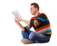 Studente maschio che legge un libro che prepara per l'esame isolato Fotografie Stock
