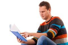 Studente maschio che legge un libro che prepara per l'esame isolato Immagini Stock Libere da Diritti