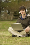 Studente maschio che per mezzo di un computer portatile all'aperto Immagine Stock