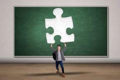 Studente maschio che porta un puzzle Fotografia Stock