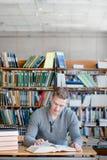 Studente maschio che prepara per l'esame in biblioteca Fotografia Stock