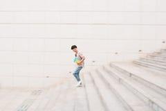 Studente maschio che scende le scale, moto vago Fotografia Stock