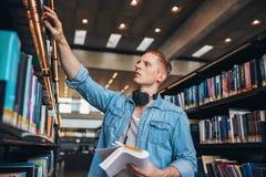 Studente maschio che seleziona libro a partire dallo scaffale delle biblioteche Immagine Stock