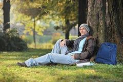 Studente maschio che si siede da un albero in parco un giorno soleggiato Immagine Stock