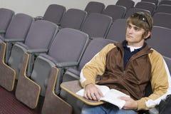 Studente maschio che si siede nell'aula vuota Fotografia Stock