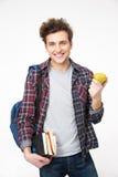 studente maschio che sta con i libri e la mela Immagini Stock