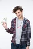 Studente maschio che sta con le fatture dei dollari Fotografia Stock