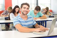 Studente maschio che utilizza computer portatile nell'aula Fotografie Stock Libere da Diritti