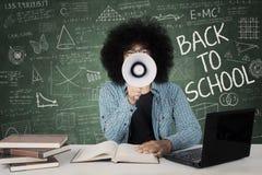 Studente maschio che utilizza megafono nell'aula Fotografie Stock