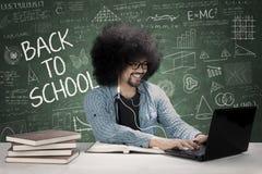 Studente maschio che utilizza trasduttore auricolare nell'aula Immagine Stock Libera da Diritti