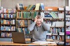 Studente maschio colpito nella biblioteca universitaria Immagini Stock