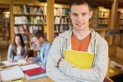 Studente maschio con altri nel fondo nella biblioteca Fotografia Stock