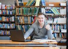 Studente maschio con il computer portatile che mostra i pollici su nella biblioteca universitaria Fotografia Stock