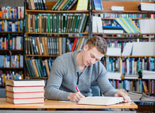 Studente maschio con il computer portatile che studia nella biblioteca universitaria Immagini Stock