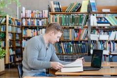 Studente maschio con il computer portatile che studia nella biblioteca universitaria Immagini Stock Libere da Diritti