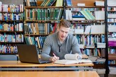 Studente maschio con il computer portatile che studia nella biblioteca universitaria Fotografie Stock Libere da Diritti