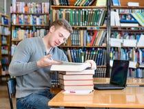Studente maschio con il computer portatile che studia nella biblioteca universitaria Immagine Stock