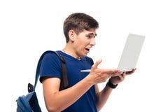Studente maschio con il computer portatile disgustato della tenuta di emozione Immagini Stock