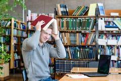 Studente maschio con il computer portatile nella biblioteca universitaria Immagine Stock