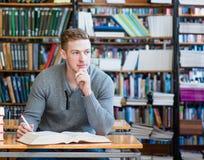 Studente maschio con il libro aperto che lavora in una biblioteca Fotografia Stock