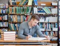 Studente maschio con il libro aperto che lavora in una biblioteca Immagini Stock Libere da Diritti