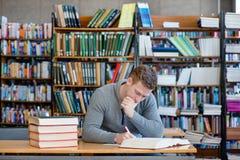 Studente maschio con il libro aperto che lavora in una biblioteca Fotografia Stock Libera da Diritti