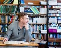 Studente maschio con il libro aperto che lavora in una biblioteca Fotografie Stock Libere da Diritti