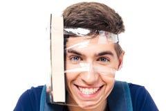 Studente maschio con il libro attaccato alla sua testa Fotografie Stock