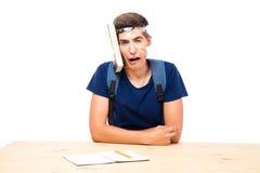 Studente maschio con il libro attaccato alla sua testa Fotografie Stock Libere da Diritti