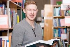 Studente maschio con il libro in biblioteca che esamina macchina fotografica Immagine Stock