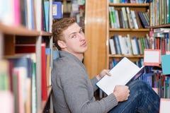 Studente maschio con il libro che si siede sul pavimento in biblioteca Immagine Stock Libera da Diritti
