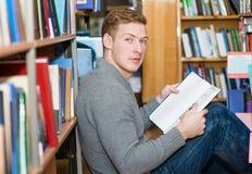 Studente maschio con il libro che si siede sul pavimento in biblioteca Immagini Stock Libere da Diritti