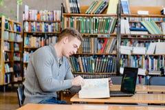 Studente maschio con il libro di lettura del computer portatile nella biblioteca universitaria Immagine Stock Libera da Diritti