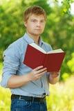 Studente (maschio) con il libro di lettura di vetro Immagine Stock