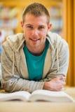 Studente maschio con il libro sul pavimento della biblioteca di istituto universitario Fotografie Stock