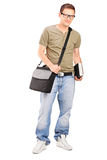 Studente maschio con la borsa di spalla che tiene un libro Immagini Stock