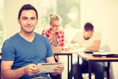 Studente maschio con la compressa davanti ai suoi compagni di classe Fotografia Stock Libera da Diritti