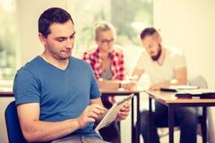 Studente maschio con la compressa davanti ai suoi compagni di classe Immagini Stock