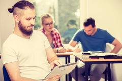 Studente maschio con la compressa davanti ai suoi compagni di classe Fotografia Stock