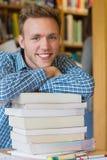 Studente maschio con la pila di libri alla biblioteca Fotografia Stock