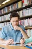 Studente maschio con la rete del pc della compressa in biblioteca Immagini Stock