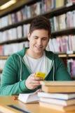 Studente maschio con lo smartphone che manda un sms nella biblioteca Fotografie Stock