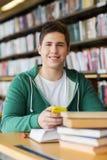 Studente maschio con lo smartphone ed i libri in biblioteca Fotografia Stock