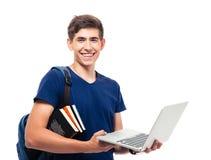 studente maschio con lo zaino ed i libri che tengono lapto Fotografia Stock