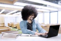 Studente maschio con un computer portatile e un trasduttore auricolare Fotografia Stock
